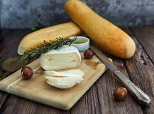 K?se auf einem Holztisch mit Oliven und Brot stockfotografie