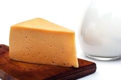 Käse auf einem Küchenbrett, ein Krug Milch lizenzfreie stockfotos