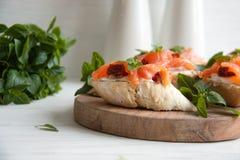 Käse des Stangenbrots mit Sahne, Lachs, trocknete Tomaten und Basilikum Stockfotos