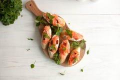 Käse des Stangenbrots mit Sahne, Lachs, trocknete Tomaten und Basilikum Stockbild