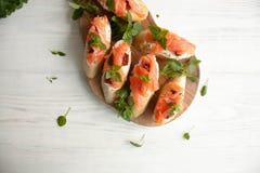 Käse des Stangenbrots mit Sahne, Lachs, trocknete Tomaten und Basilikum Lizenzfreies Stockbild