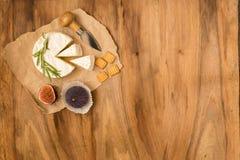 Käse diente mit Feigen, Crackern und Kräutern auf einem hölzernen Hintergrund Stockbild