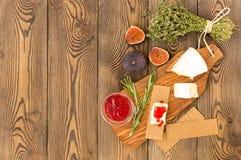 Käse diente mit Stau, Feigen, Crackern und Kräutern auf einem hölzernen Hintergrund Stockbilder