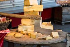Käse für Verkauf und ein alter Schneider oder ein Zerhacker benutzt für das Schneiden von Käsen in einem Markt in Salzburg Stockfotos