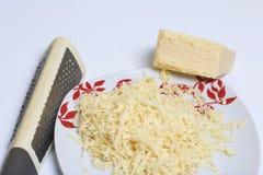 Käse, gehackt auf einer Reibe Hackfleischsteaks mit Kartoffeln, Eiern und Käse Kochen von Schritten und von Bestandteilen lizenzfreie stockfotografie