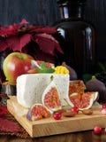 Käse gemacht von der Schafmilch und von den Scheiben von Feigen auf einem hölzernen Brett umgeben durch Moosbeeren und Mandel Lizenzfreies Stockfoto