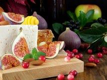 Käse gemacht von der Schafmilch und von den Scheiben von Feigen auf einem hölzernen Brett umgeben durch Moosbeeren und Mandel Stockfotos