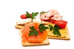 Käse, Lachs, Garnelen auf Crackern Lizenzfreie Stockfotografie