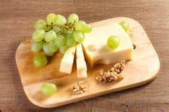 Käse mit Bürste von Trauben und Stockfotos