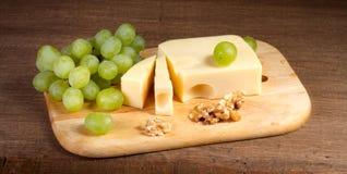 Käse mit Bürste von Trauben und von Walnüssen Lizenzfreies Stockfoto