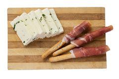 Käse mit Grüns und Breadsticks mit Prosciutto auf einem hölzernen Brett lizenzfreie stockbilder
