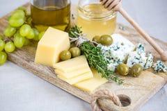 Käse mit Honig und Trauben Stockfotografie