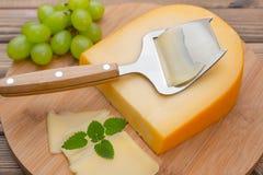 Käse mit Messer an Bord Stockfoto