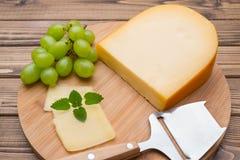 Käse mit Messer an Bord Lizenzfreie Stockfotografie