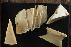 Käse schneidet Draufsicht gegen einen Hintergrund des Naturschiefers Lizenzfreie Stockfotos