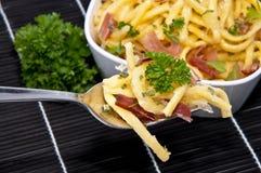 Käse Spaetzle auf schwarzer Tischdecke Stockbilder
