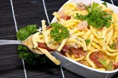 Käse Spaetzle auf schwarzer Tischdecke Stockfotografie
