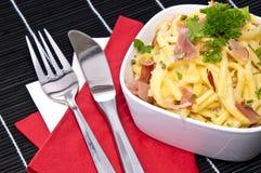 Käse Spaetzle mit Tischbesteck (auf Schwarzem) Stockbilder