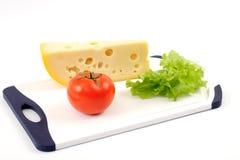 Käse, Tomate und Salat bedecken auf einem weißen Vorstand Stockfotos