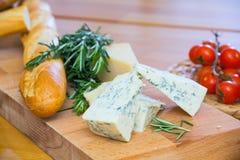 Käse und Brot auf dem hölzernen Brett Lizenzfreie Stockfotos