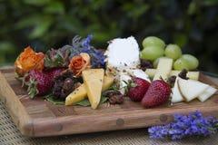 Käse-und Frucht-Platte mit frischen Blumen Lizenzfreie Stockbilder