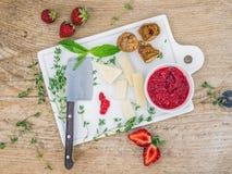 Käse und Frucht stellten auf ein weißes keramisches Schneidebrett ein Stockfotografie