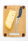Käse und Messer auf einem hölzernen Vorstand Stockfotografie