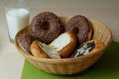 Käse und Mohnblumenkuchen- und -schokoladenschaumgummiringe mit einem Glas Milch Stockfotografie