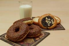 Käse und Mohnblumenkuchen- und -schokoladenschaumgummiringe mit einem Glas Milch Stockbild