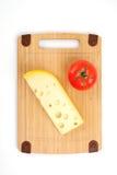 Käse und Tomate auf einem hölzernen Vorstand. Lizenzfreies Stockbild