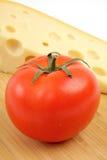 Käse und Tomate auf einem hölzernen Vorstand. Stockfotografie