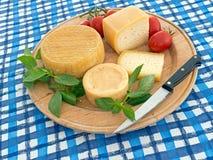 Käse und Tomate auf rundem hölzernem Brett, auf blauem und weißem Stoff Lizenzfreie Stockbilder