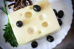 Käse und Walnüsse auf einer Platte Stockbilder