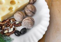 Käse und Walnüsse auf einer Platte Stockfotografie