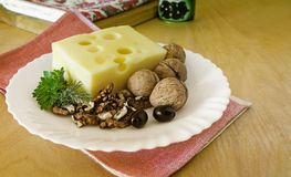 Käse und Walnüsse auf einer Platte Lizenzfreie Stockfotos