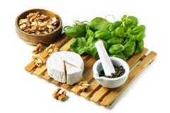 Käse und Walnüsse mit Basilikum Stockfotografie