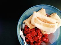 Käseblinchiki/-krepps auf einer Platte mit Sauerkirschen Stockfotografie