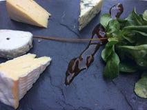 Käsebrett mit Essiggurke auf einem Schiefer stockbild