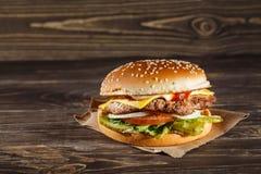Käseburger mit gegrilltem Fleisch, Käse, Tomate, auf Kraftpapier Lizenzfreies Stockfoto