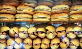 Käseburger und Hotdogs in einem Schaukasten Lizenzfreie Stockfotos