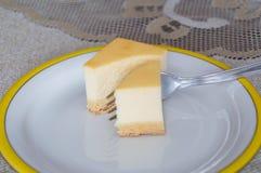 Käsekuchen auf weißer Platte mit Gabel Stockfotografie