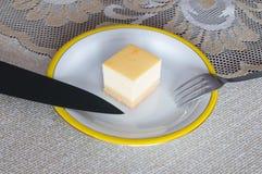 Käsekuchen auf weißer Platte mit Gabel Stockbild