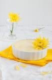 Käsekuchen in der keramischen Schüssel mit gelben Blumen Lizenzfreie Stockfotos