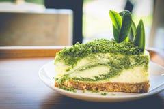 Käsekuchen des grünen Tees auf weißem Teller Stockfotografie