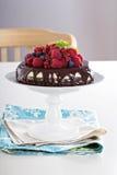Käsekuchen mit Beeren auf einer Schokoladenkuchenschicht Stockfoto