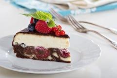 Käsekuchen mit Beeren auf einer Schokoladenkuchenschicht Lizenzfreie Stockfotografie