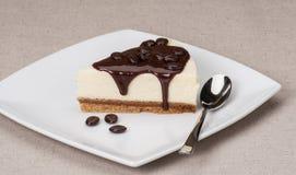 Käsekuchen mit Schokoladen-Soße auf weißer Platte Lizenzfreies Stockfoto