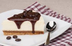 Käsekuchen mit Schokoladen-Soße auf weißer Platte Stockbilder