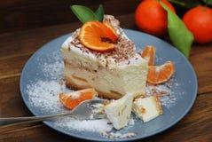 Käsekuchen mit Tangerine-Frucht auf Grey Plate und Sugar Powder Dunkler Holztisch und Gabel Eatting-Prozess Stockfoto