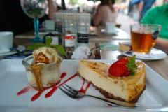 Käsekuchen mit Vanilleeis- und Karamellsoße Stockbild